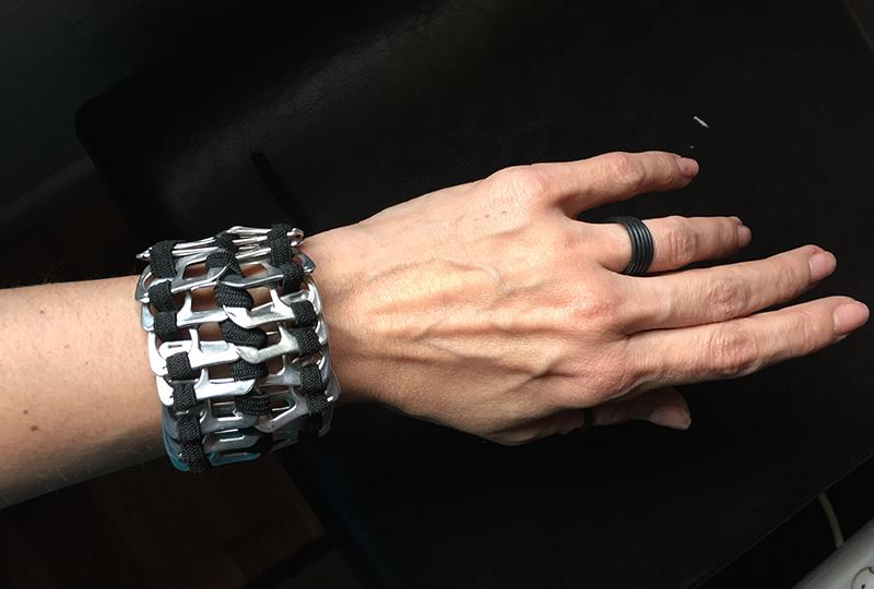 Pulsera hecha con las anillas de las latas y elástico negro